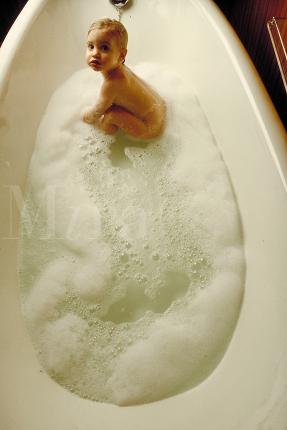 Baby frolicking in bubble bath in bathtub. Baby. Douglaston NY.