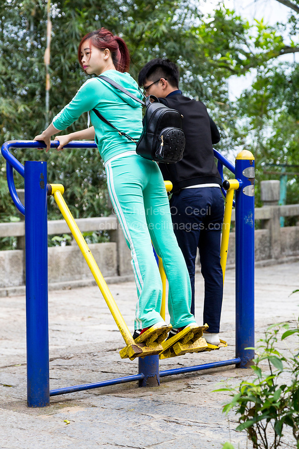 Yangshuo, China.  Young Couple Working Out on Public Exercise Equipment.