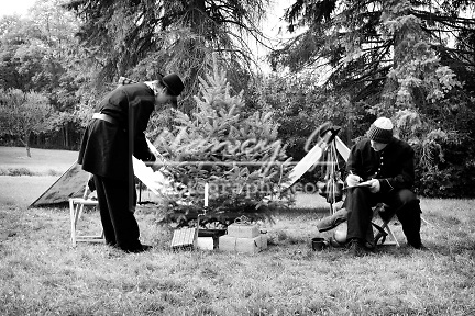 Young Civil War soldier reenactors at Christmas time decorating a Christmas tree with garland and writing letter home