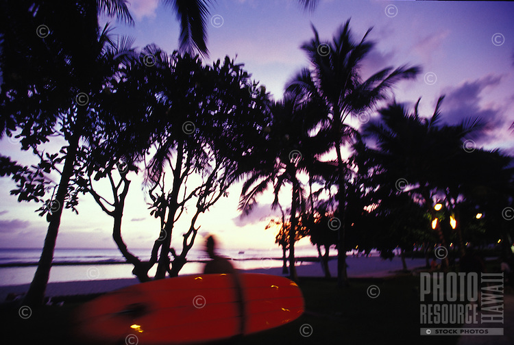 Surfer with red board walking along Kalakaua Boulevard in Waikiki at sunset, ocean and trees in background