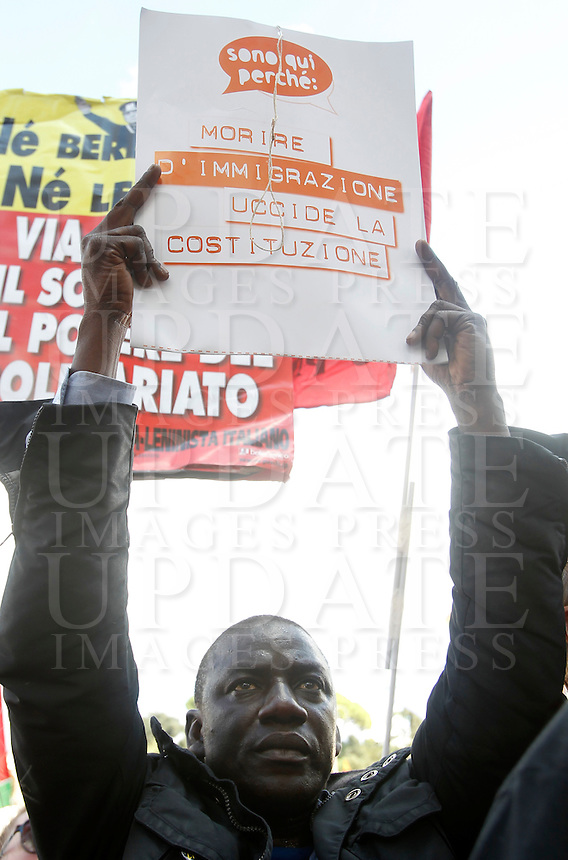 """Manifestazione """"La via maestra"""" in difesa della Costituzione Italiana a Roma, 12 ottobre 2013.<br /> A demonstrator holds a sign reading """"I am here because dying for immigration kills constitution"""" during a rally in defence of the Italian Constitution in Rome, 12 October 2013.<br /> UPDATE IMAGES PRESS/Isabella Bonotto"""