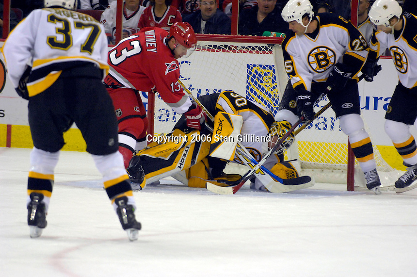 Boston Bruins' goalie Tim Thomas defends a rush by the Carolina Hurricanes' Ray Whitney (13) helped by teammate Andrew Alberts (41) during an NHL hockey game Saturday, Dec. 2, 2006 in Raleigh, N.C. Carolina won 5-2.<br />