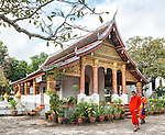 Two monks in traditional orange robes pass in front of the temple at Wat Sop Sickharam, a Buddhist temple and monastery in Luang Prabang, Laos.