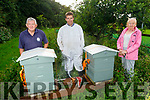 Joe Moynihan with beekeeper Daithi Creedon and Freda Conroy as they open the beehive on the Manor Village walkway on Friday.