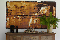 A rusty metal artwork hanging above a small cabinet in designerJames Huniford's home