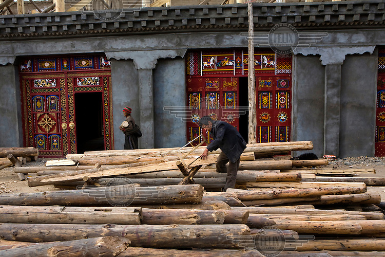 A workman smokes and saws timber for construction in a village in the west of the province.