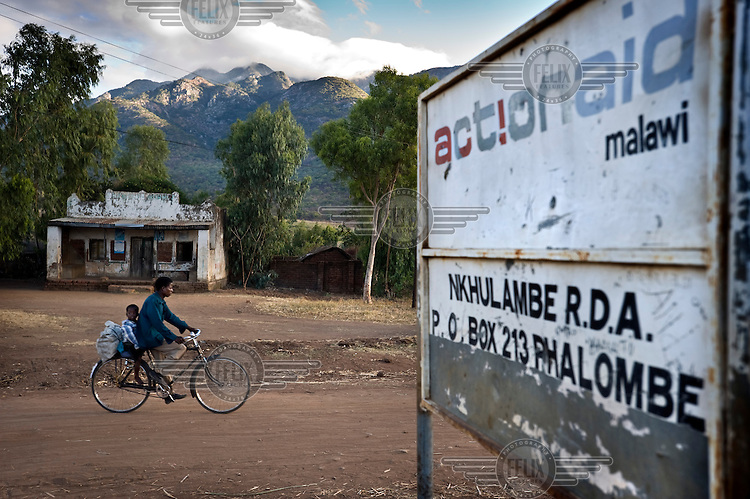 A young man rides a bicycle past a sign for ActionAid Malawi in Phalombe district.