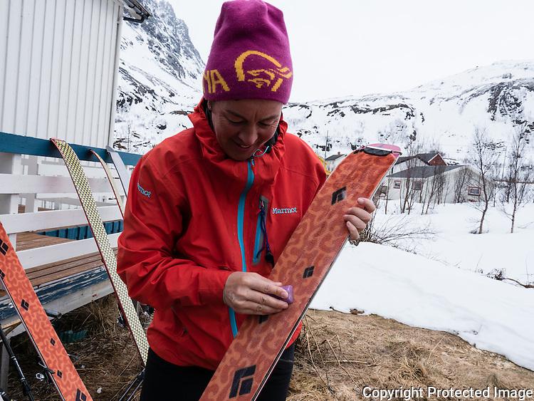 Dame smører skifeller med glidvoks. ---- Woman waxing ski furs.