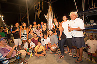 A group pose with a Pacific blue marlin grander at Honokohau Harbor, Kailua-Kona, Big Island.