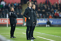 (L-R) Billy Reid, assistant manager, Graham Potter, manager, and Bjorn Hamberg, assistant coach for Swansea stand on the touch line during the Sky Bet Championship match between Swansea City and Wigan Athletic at the Liberty Stadium, Swansea, Wales, UK. Saturday 29 December 2018