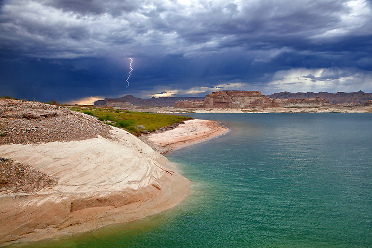 Viewed from the Lone Rock area of Lake Powell in Arizona, a lightning bolt emerges over the cliffs of the Grand Staircase-Escalante National Monument in Utah.