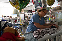 Staff nurse Julie Briere cares for a patient at the Neonatal Intensive Care Unit at Boston Children's Hospital in Boston, Mass., on Mon., June 13, 2016. In the background, the NICU team has a meeting discussing patient cases during rounds. Patients, family space, and work space is all crowded together in the current NICU. The NICU will be greatly expanded under building plans for the hospital, but those plans will eliminate the Prouty Garden, a half-acre of green space at the hospital that many in the hospital community hold dear.