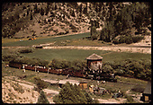 Elevated view of RGS #74 at Brown water tank with Rocky Mountain Railroad Club (RMRRC) trip.  Consist is #74, cabooses #0400 &amp; #0401, three gondolas and business car B-20 &quot;Edna&quot;.  A threshing machine is parked between the sheds.<br /> RGS  Brown, CO  Taken by Pfeifer, Jack A. - 9/1/1951