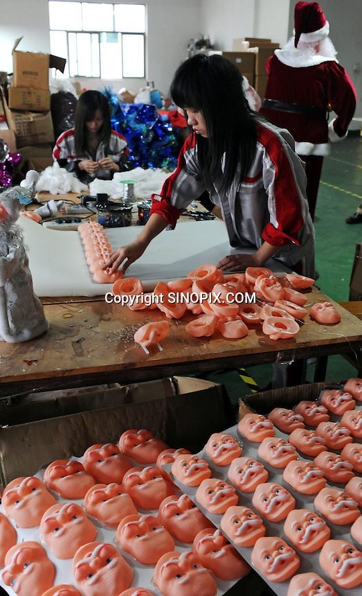 Santa's faces are prepared for installation that will be fitted into dancing Santas at a medium sized factory in Yi Wu, China.  Yi Wu exports 40-50 % of the entire European Christmas decorations and 70 % of US and Mexico's Christmas gifts come from Yi Wu.