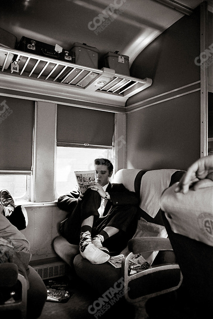 "On a train somewhere between Chatanooga and Memphis on the Southern Railroad, part of a 27-hour overnight train trip. Elvis is reading a comic book, ""Archie and Veronica"", there are other comic books around. He is wearing white bucks and argyle socks. His friend Junior Smith is sleeping slightly out of frame, his hand is at right. USA. Early July 4, 1956"