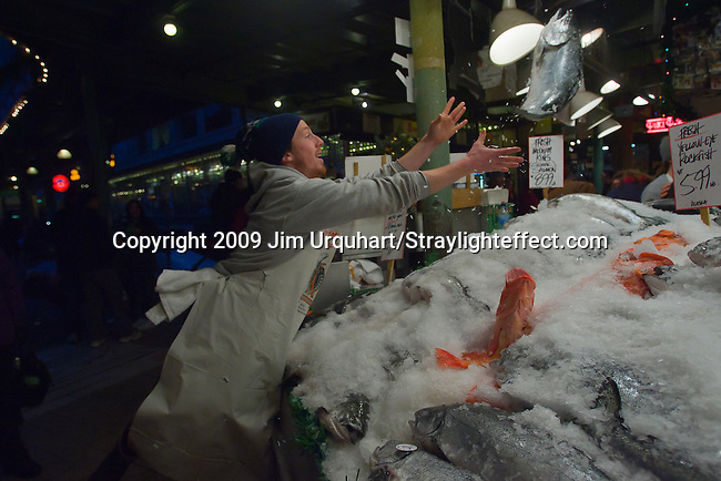 Jim Urquhart/Straylighteffect.com Fish monger Ryan Rector throws a salmon at the Pike Place Fish Market at the Pike Place Market in Seattle, Washington. 12/22/2009 - Jim Urquhart/Straylighteffect.com