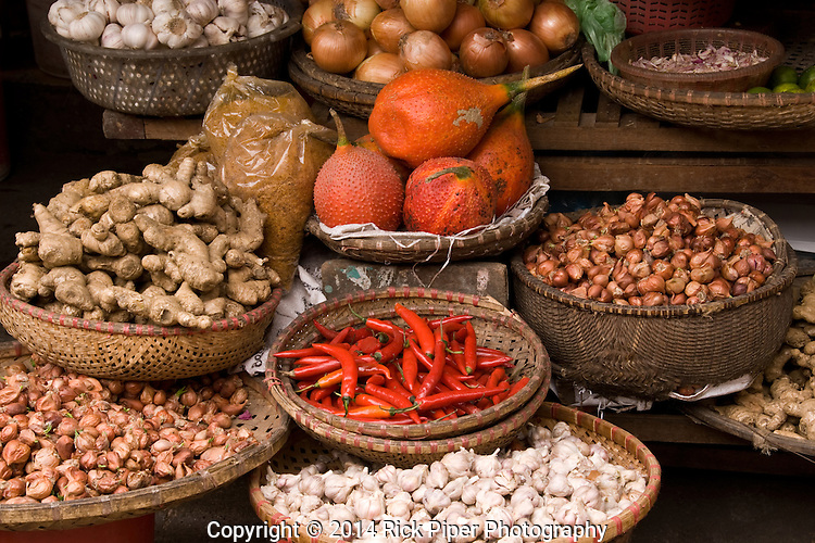 Baskets of gac fruit, chilli, onions, shallots, ginger and garlic at a market in the Hanoi Old Quarter, Viet Nam