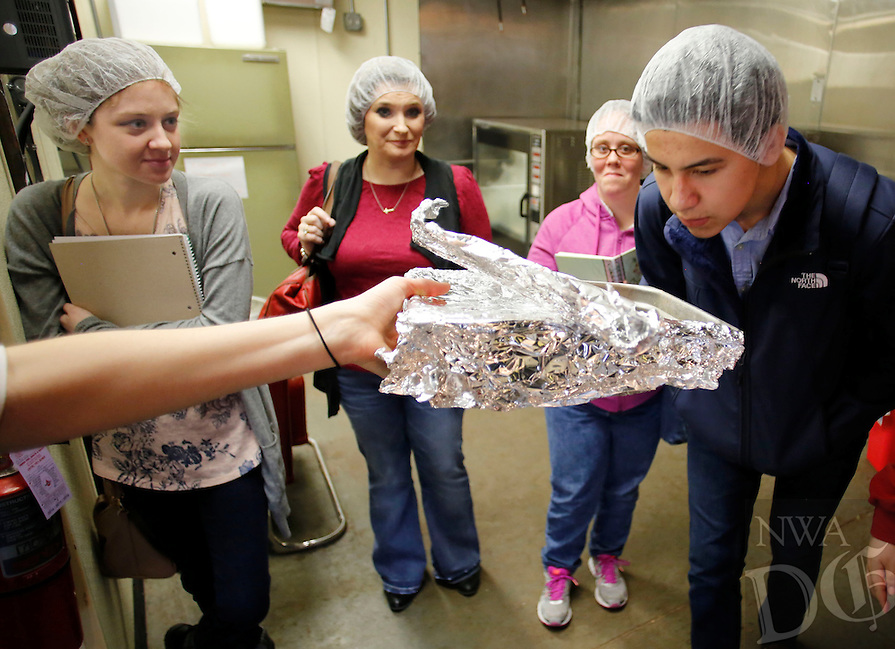 NWA Democrat-Gazette/DAVID GOTTSCHALK  Andy Serrano, a student in the Entrepreneurship in Action class at Northwest Arkansas Community College, smells chocolate Friday, February 19, 2016, from a pan held by Lauren Blanco, chief executive officer and cofounder of Hello Cocoa, inside the production room of the bean to bar chocolate producer in Fayetteville. The class, part of Enactus, an organization that enables progress through entrepreneurial action, visited the business in an effort to collect production, marketing and nutrition information to create a sustainable bean to bar company.