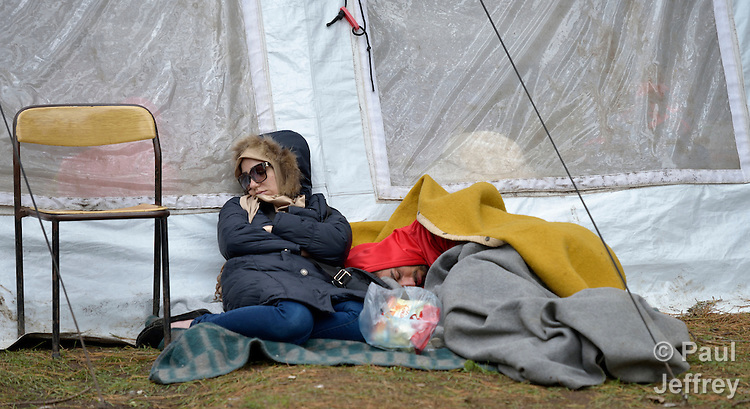 A woman sleeps outside a tent in a refugee processing center in the Serbian village of Presevo, not far from the Macedonian border. Hundreds of thousands of refugees and migrants have flowed through Serbia in 2015, on their way from Syria, Iraq and other countries to western Europe.