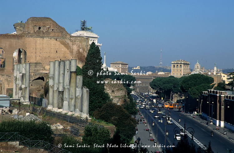 Ruins of the Roman Forum with view of busy city street, Rome, Italy.