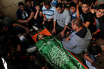 Relatives of Palestinian Mahmud Abu Jhaisha mourn next to his body before his funeral, in the West Bank city of Hebron on April 26, 2015. Mahmud Abu Jhaisha, in his 20s, died on the way to a hospital after he was shot by Israeli police after he wounded a border police officer with a knife, the day before in Hebron. Photo by Mamoun Wazwaz