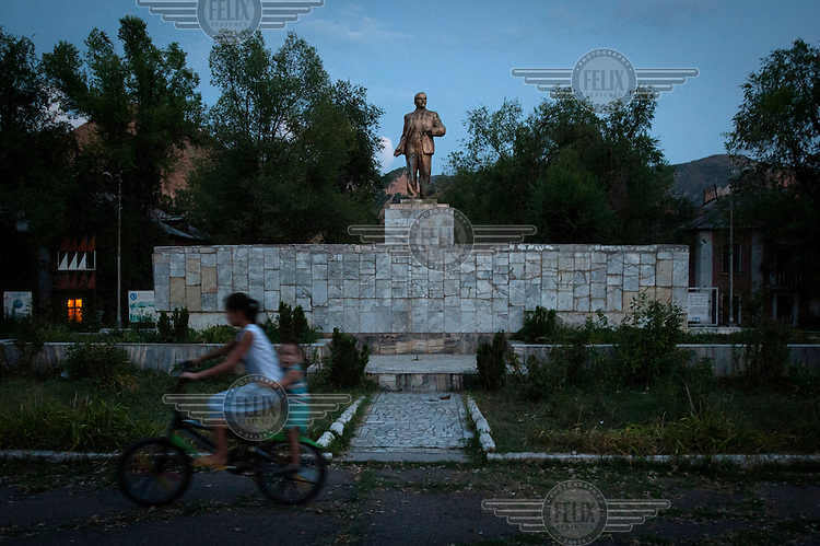 Two young girls ride a bicycle past a statue of Lenin in the town centre.