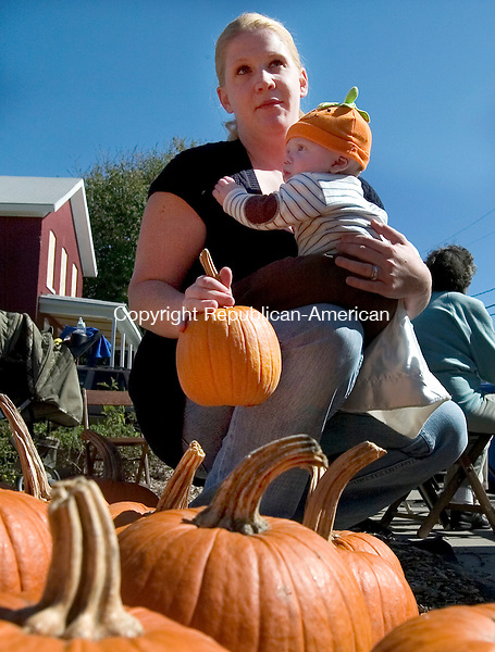 WATERBURY, CT 01 October 2008-100308SV02--Angela Coffill of Thomaston and her son Gavin Coffill, 5 months, check out the pumpkin patch at the Brass City Harvest block party. The nonprofit group established two community gardens in the Crownbrook neighborhood and celebrated its harvest year with music, the pumpkin patch and more at the harvest's garden on Burton Street in Waterbury. Coffill was visiting her mother in law in the neighborhood Saturday.<br /> Steven Valenti Republican-American