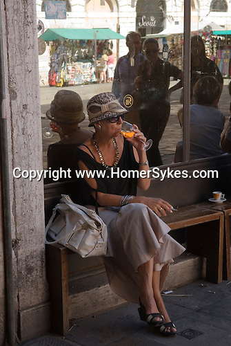 Venice Italy 2009. Woman drinking a orange drink Campari and Soda Campo Cesare Battisti.