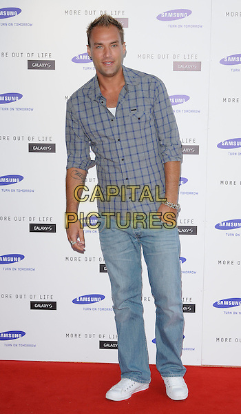 CALUM BEST .attends the launch of the Samsung Galaxy S Smartphone held at Altitude Bar, London, England, UK, .June 15th, 2010. .full length grey gray plaid checked check shirt jeans white trainers tattoo hand in pocket .CAP/CAN.©Can Nguyen/Capital Pictures.
