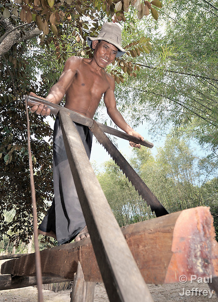 Sor Soch cuts lumber in the Cambodian village of Solang Kandal.