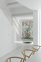 A wall at the foot of the staircase beyond the open plan dining area is decorated in a Chinese wallpaper by Zuber