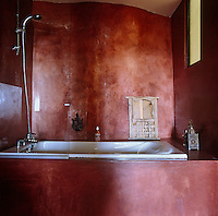 A dramatic bathroom with a red tadelakt wall finish