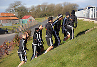 Pictured: Players walk to the training pitch Thursday 25 February<br />