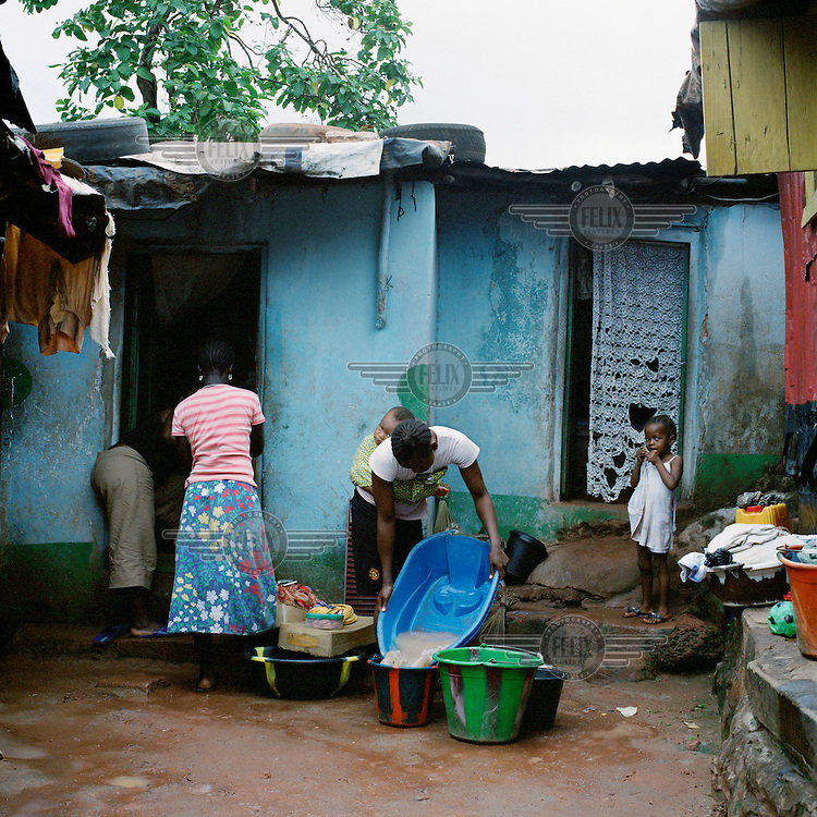 A young mother does house work in front of her house in Kroo Bay with her baby starpped to her back. Kroo Bay, a slum built on a rubbish dump on the eastern outskirts of the capital Freetown, houses around 6,500 people.