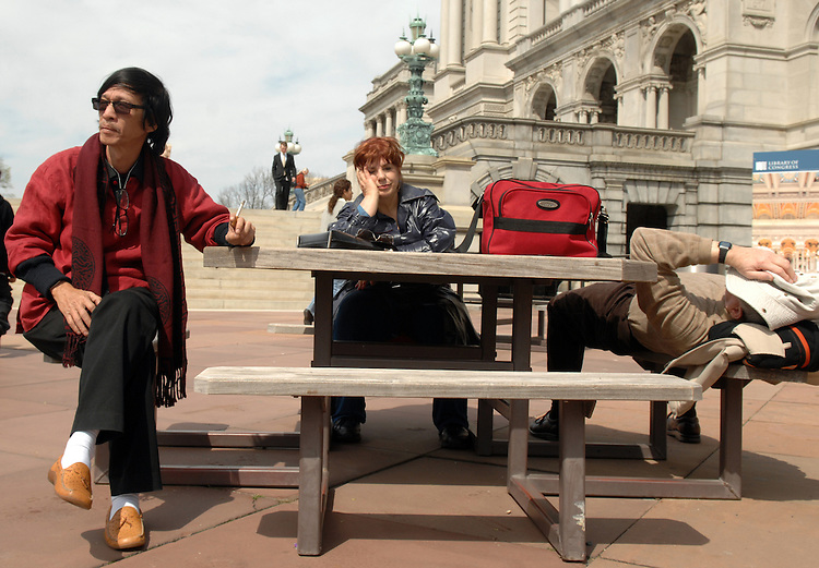 Tourists including Mike Walker, right, and Barbara Halpern of Michigan, take a break  outside of the Thomas Jefferson Building of the Library of Congress.