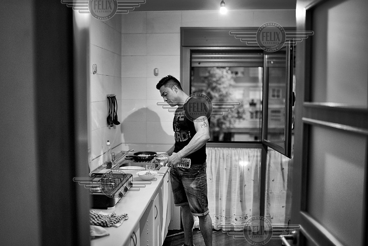 A man pours a glass of water in the kitchen in the squatted luxury building known as 'Corrala Utopia'.
