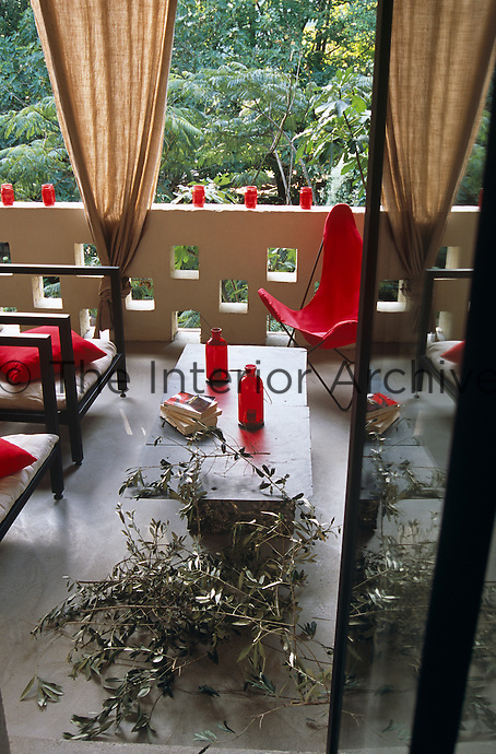 Candle holders fashioned out of red glass bottles and jars line the walls of the terrace around a coffee table made from a recycled sheet of metal