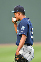 Starting pitcher Erick Julio (29) of Asheville Tourists kisses the ball as he warms up before a game against the Greenville Drive on Wednesday, May 3, 2017, at Fluor Field at the West End in Greenville, South Carolina. Greenville won, 8-0. (Tom Priddy/Four Seam Images)