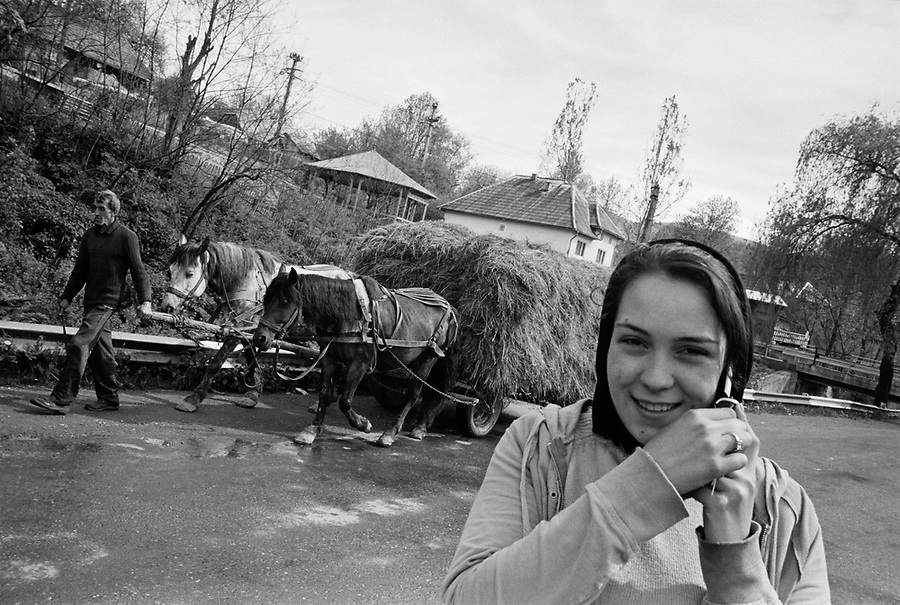 ROMANIA / Maramures / Valeni / May 2008..Ileana Nemes, 15, talks on a mobile phone in the village center while her father, Stefan, 50, brings home a haystack. Mobile phones only recently arrived and have dramatically changed communication in the village since most inhabitants never even had fixed line service which was available starting in 2002...© Davin Ellicson / Anzenberger