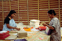 Workers packing bed linens for export at manufacturing plant, Kerala state, India