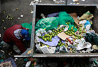 BOGOTA, COLOMBIA - April 17: A man wearing as face mask searches for leftovers of rotten fruits and vegetables in a trash dumpster in Corabastos, the main food distribution center of the country, on April 17, 2020 in Bogota, Colombia. Alimentary aid offered by the National government has not reached yet the poorest families, amid the coronavirus crisis. (Photo by John W. Vizcaino/VIEWpress)