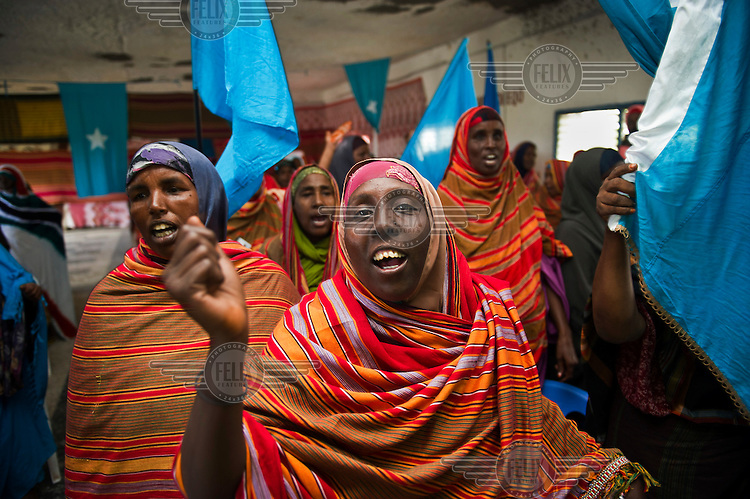 Women sing during a ceremony, holding the national flag.
