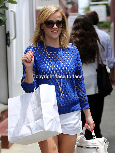 Reese Witherspoon gets photo-bombed by a paparazzo while out shopping at the Brentwood County Mart. The pap was sad that he didn't get a picture so he left his imprint by jumping the picture. Reese is wearing summerly white shorts with white Proenza Schouler bag and blue crochet sweater. Los Angeles, California on July 7, 2013<br />