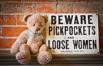 A stuffed teddy bear sits next to a funny sign in front of a red brick wall.