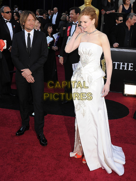 KEITH URBAN & NICOLE KIDMAN .arriving at the 83rd Annual Academy Awards at the Kodak Theatre in Los Angeles, California, USA,.February 27th, 2011..oscars arrivals  full length black suit tie strapless white dress hand touching face couple husband wife beaded orange peep toe shoes peplum .CAP/ROT/TM.©TM/Roth Stock/Capital Pictures