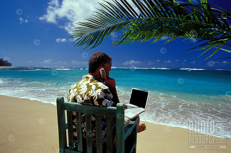 Man working on laptop computer talking on cellular phone, in aloha shirt, at a beach under a palm tree