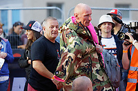Pictured: Gareth Thomas is helped to wear a camouflage jacket by his husband Stephen (L) after crossing the finish line. Sunday 15 September 2019<br /> Re: Ironman triathlon event in Tenby, Wales, UK.