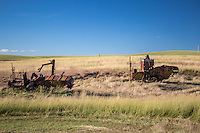 Old farm equipment setting in a fileld in the Palouse.  The Palouse Is a region of where there are no continuous valleys, and the hills do not connect to make long ridges. These hills were not created by rivers and streams, as is most of our landscape, but formed more like sandunes, with winds depositing silt to form of some of the most fertile soil in the country.