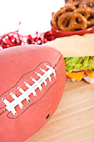 Football on table with sandwich and pretzel snacks.