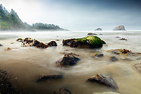 Waves wash over the rocks on a cloudy morning at False Klamath Cove in Redwood National and State Parks.